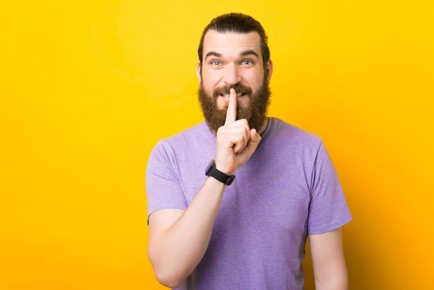 Młody brodaty mężczyzna wykonuje gest ciszy lub ciszy.