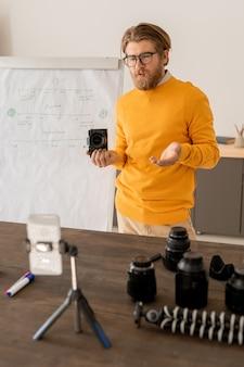 Młody brodaty mężczyzna z aparatem fotograficznym wyjaśnia, jak robić zdjęcia swoim odbiorcom online przed aparatem w smartfonie