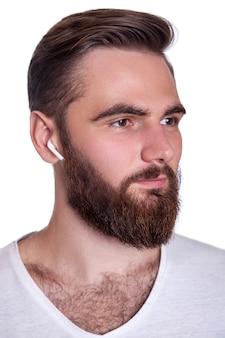 Młody brodaty mężczyzna z bezprzewodowymi słuchawkami na uszach. strzał studio, na białym tle.
