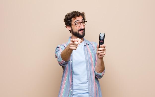 Młody brodaty mężczyzna z elektryczną żyletką