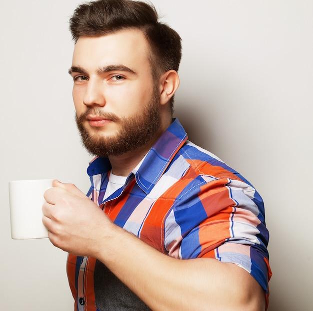 Młody brodaty mężczyzna z filiżanką kawy na szarym tle