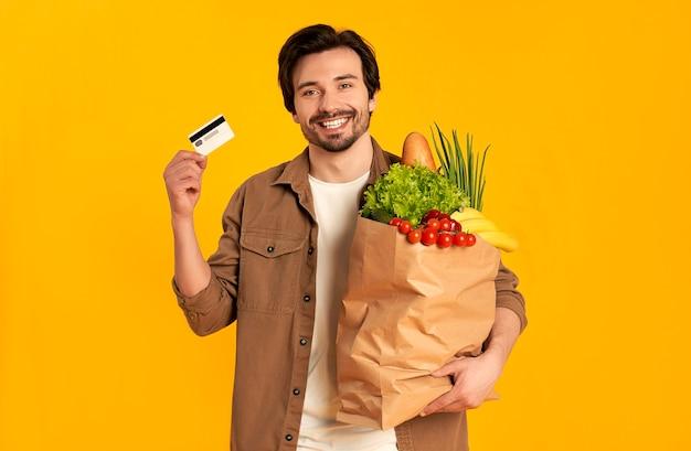 Młody brodaty mężczyzna z kartą kredytową i papierową torbą jedzenia na białym tle.