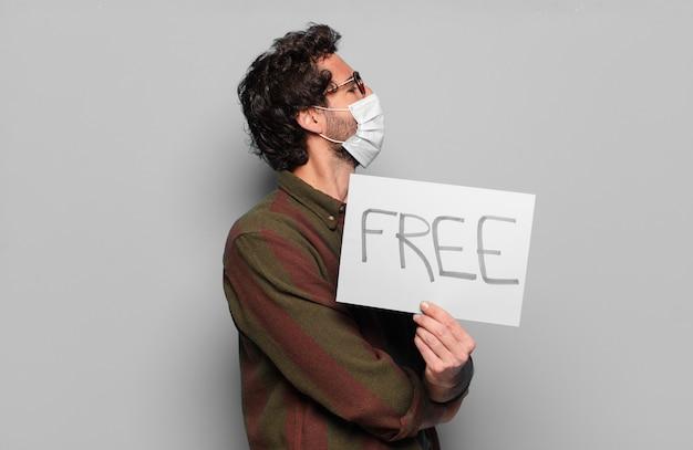 Młody brodaty mężczyzna z maską medyczną i bezpłatną wyżywieniem