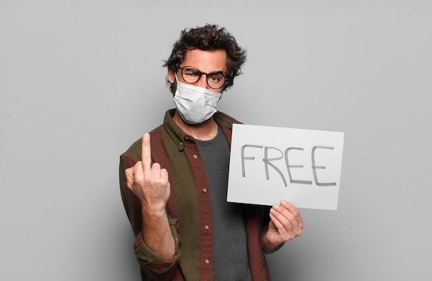 Młody brodaty mężczyzna z maską medyczną i bezpłatnym sztandarem