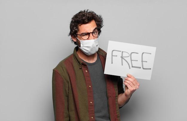 Młody brodaty mężczyzna z maską medyczną i koncepcją bezpłatnego sztandaru