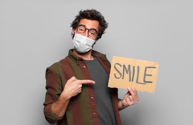 Młody brodaty mężczyzna z maską medyczną i koncepcją uśmiechu