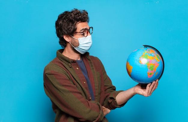 Młody brodaty mężczyzna z maską medyczną i modelem mapy świata
