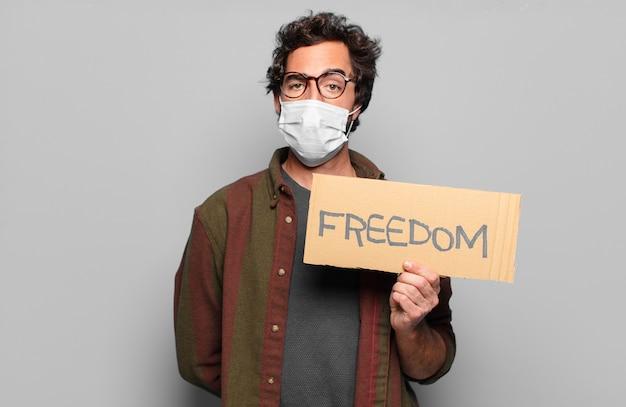 Młody brodaty mężczyzna z maską medyczną i tablicą wolności