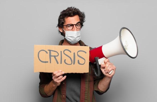 Młody brodaty mężczyzna z maską medyczną, megafonem i tablicą kryzysową