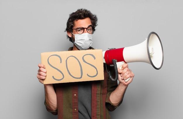 Młody brodaty mężczyzna z maską medyczną, megafonem i tablicą sos