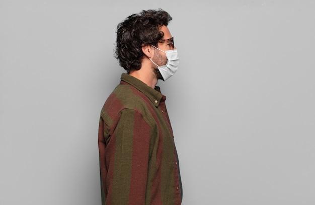 Młody brodaty mężczyzna z maską medyczną