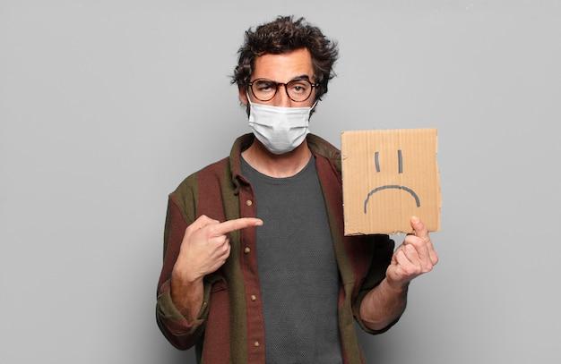 Młody brodaty mężczyzna z medyczną maską i koncepcją smutny transparent