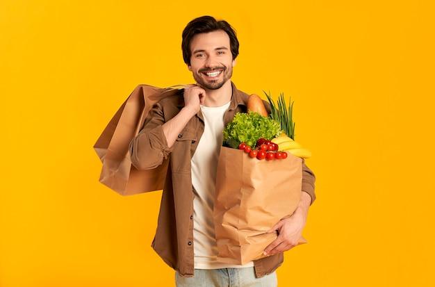 Młody brodaty mężczyzna z papierową torbą warzyw spożywczych i zakupów na białym tle.