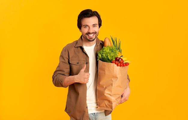 Młody brodaty mężczyzna z papierowym opakowaniem produktów warzywnych pokazuje kciuki do góry gest na białym tle.