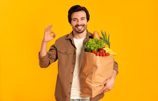 Młody brodaty mężczyzna z papierowym opakowaniem produktów warzywnych pokazuje ok gest na białym tle.