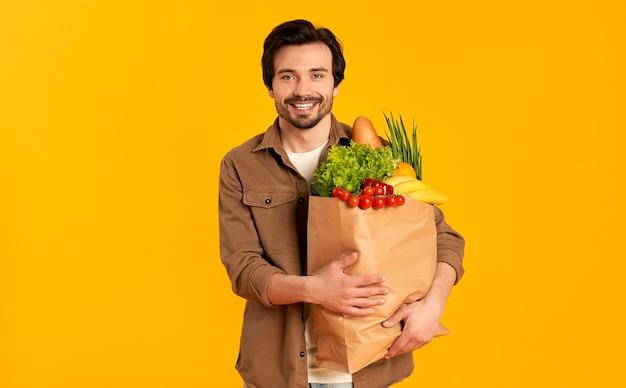 Młody brodaty mężczyzna z papierowym pakietem warzyw spożywczych na białym tle.