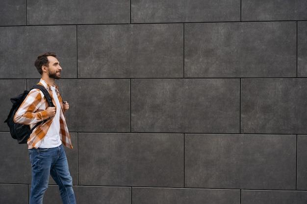 Młody brodaty mężczyzna z plecakiem spaceru na ulicy, na białym tle. koncepcja podróży