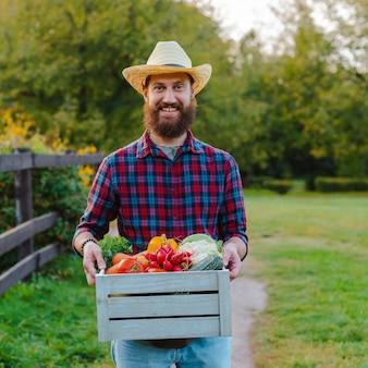 Młody brodaty mężczyzna z pudełkiem świeżych ekologicznych warzyw