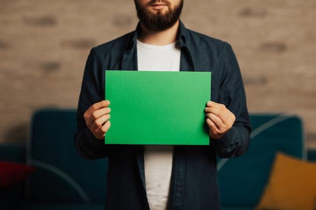 Młody brodaty mężczyzna z pustym zielonym sztandarem.