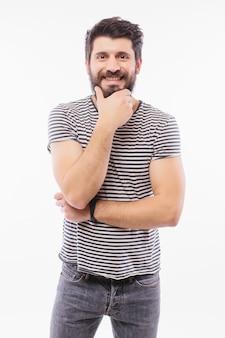 Młody brodaty mężczyzna z rękami skrzyżowanymi na szarej ścianie