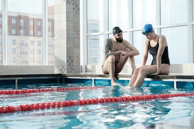Młody brodaty mężczyzna z tatuażem siedzi na krawędzi basenu i wspiera innego pływaka
