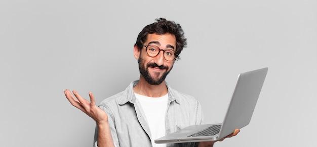 Młody brodaty mężczyzna zdezorientowany wyrazem twarzy z laptopem