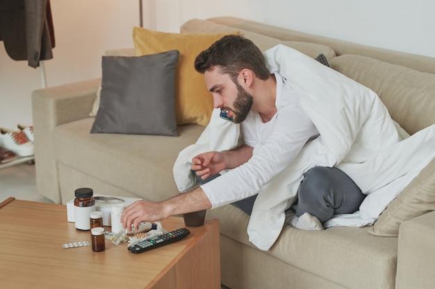 Młody brodaty mężczyzna ze smartfonem dzwoni do pracy, aby ostrzec o swojej chorobie i zostać w domu, pochylając się nad stołem z lekarstwami