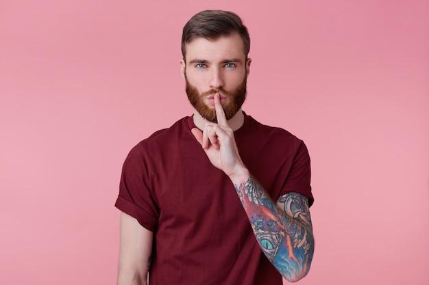 Młody brodaty młody mężczyzna z wytatuowaną ręką trzyma palec wskazujący na ustach, wzywa do zachowania tajemnicy, nikomu nie mówi, nie hałasuje, demonstruje gest ciszy, odizolowany na różowym tle.