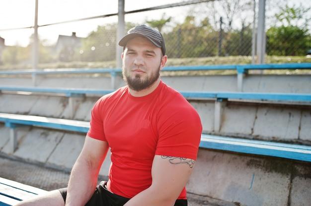 Młody brodaty muskularny mężczyzna nosić czerwoną koszulę, szorty i czapkę na stadionie