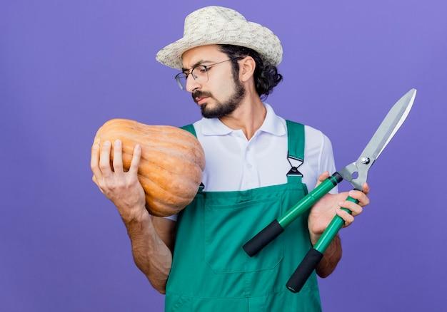 Młody brodaty ogrodnik mężczyzna ubrany w kombinezon i kapelusz, trzymając dyni i nożyce do żywopłotu, patrząc niezadowolony