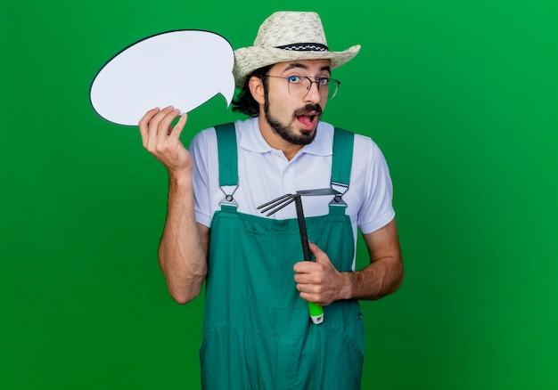 Młody brodaty ogrodnik mężczyzna ubrany w kombinezon i kapelusz, trzymając macka i pusty znak dymku jest zaskoczony