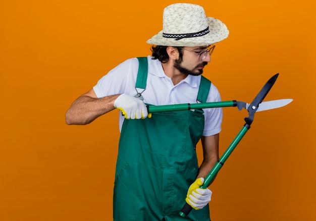 Młody brodaty ogrodnik mężczyzna ubrany w kombinezon i kapelusz trzymając nożyce do żywopłotu patrząc na maszynki do strzyżenia z poważną miną