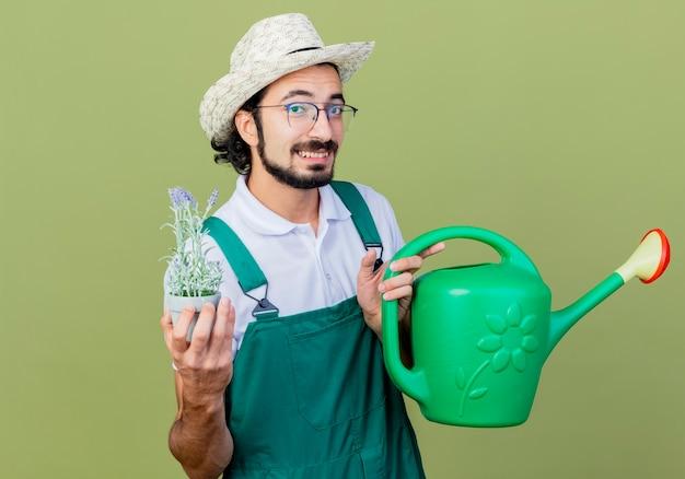 Młody brodaty ogrodnik mężczyzna ubrany w kombinezon i kapelusz trzymający konewkę i doniczkową roślinę patrząc z przodu uśmiechnięty z radosną twarzą stojącą nad jasnozieloną ścianą