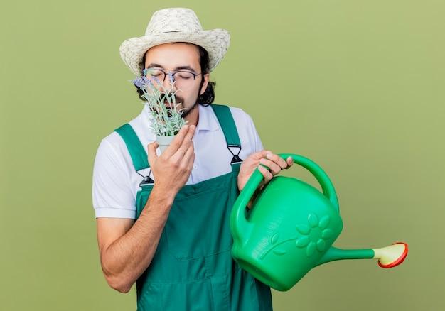 Młody brodaty ogrodnik mężczyzna ubrany w kombinezon i kapelusz trzymający konewkę i roślinę doniczkową wdychający przyjemny zapach stojący nad jasnozieloną ścianą