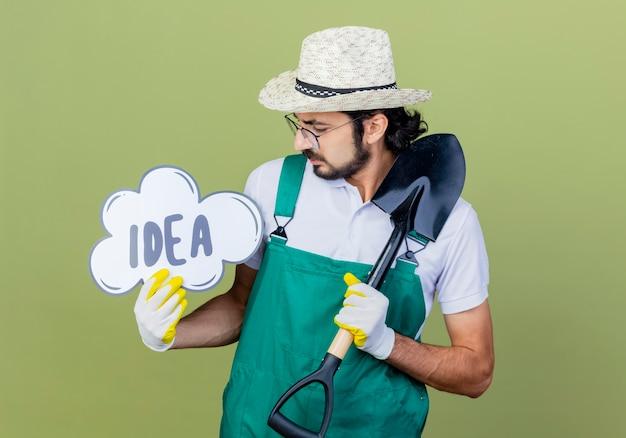 Młody brodaty ogrodnik mężczyzna ubrany w kombinezon i kapelusz trzymający łopatę i znak dymku z pomysłem na słowo, patrząc na niego zdziwiony stojąc nad jasnozieloną ścianą