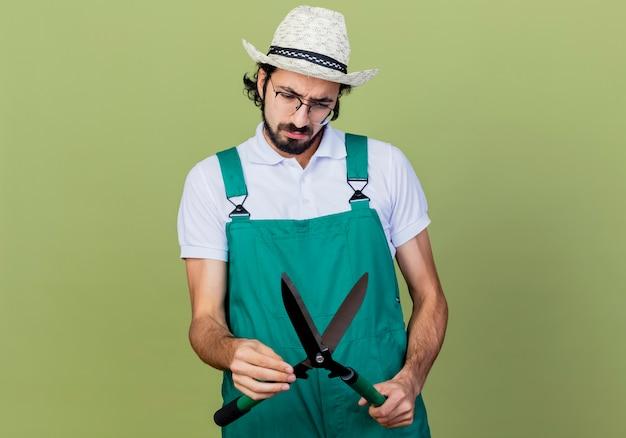 Młody brodaty ogrodnik mężczyzna ubrany w kombinezon i kapelusz trzymający nożyce do żywopłotu patrząc na niego zdziwiony stojąc nad jasnozieloną ścianą