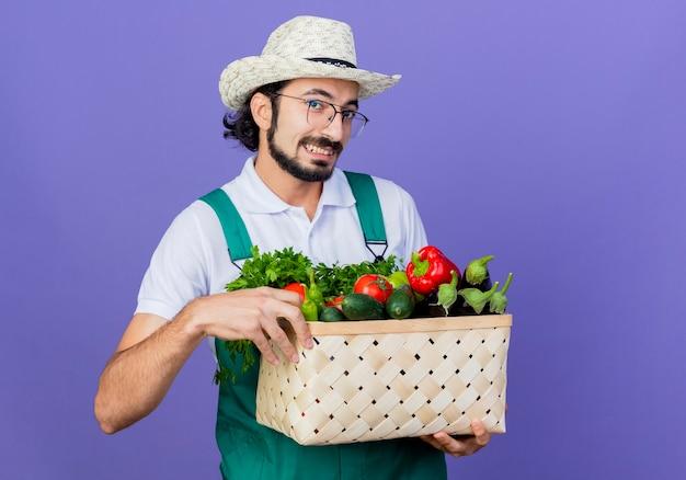 Młody brodaty ogrodnik mężczyzna ubrany w kombinezon i kapelusz trzymający skrzynię pełną warzyw patrząc z przodu uśmiechnięty wesoło stojąc nad niebieską ścianą