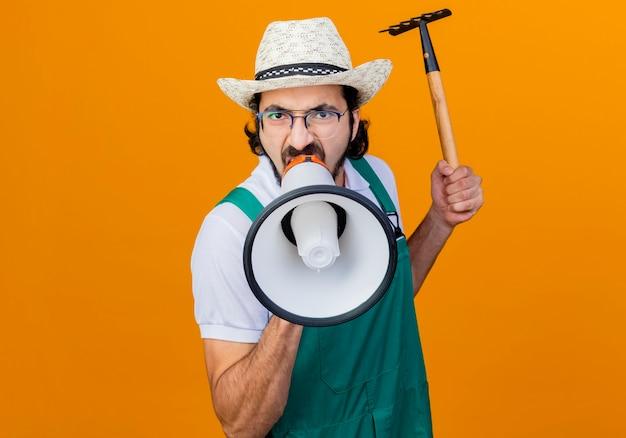 Młody brodaty ogrodnik mężczyzna w kombinezonie i kapeluszu trzymający mini grabie krzyczący do megafonu z agresywnym wyrazem twarzy stojący nad pomarańczową ścianą
