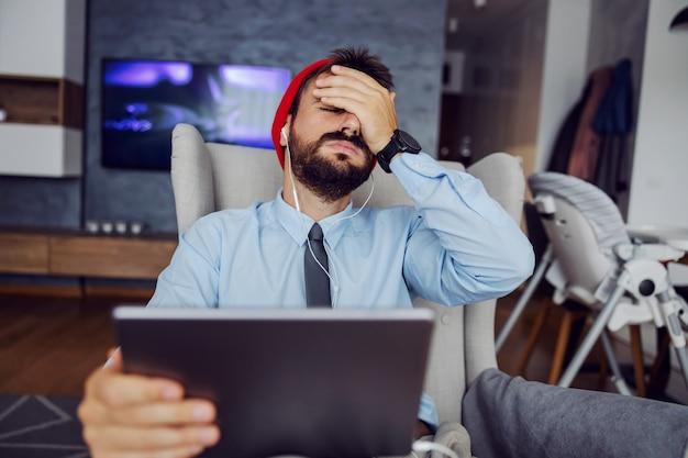 Młody brodaty ojciec ubrany biznesowy dorywczo siedząc w domu, używając tabletu i mając dłoń na twarzy. w pracy wydarzył się straszny błąd.