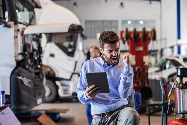 Młody brodaty podekscytowany szef trzyma tablet i wiwatuje do sukcesu. garaż wnętrza firmy spedycyjnej.