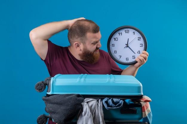 Młody brodaty podróżnik z walizką pełną ubrań trzyma zegar ścienny patrząc na niego zdezorientowany drapiąc się po głowie