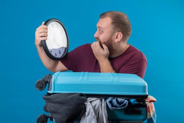 Młody brodaty podróżnik z walizką pełną ubrań, trzymając zegar ścienny patrząc na niego w panice