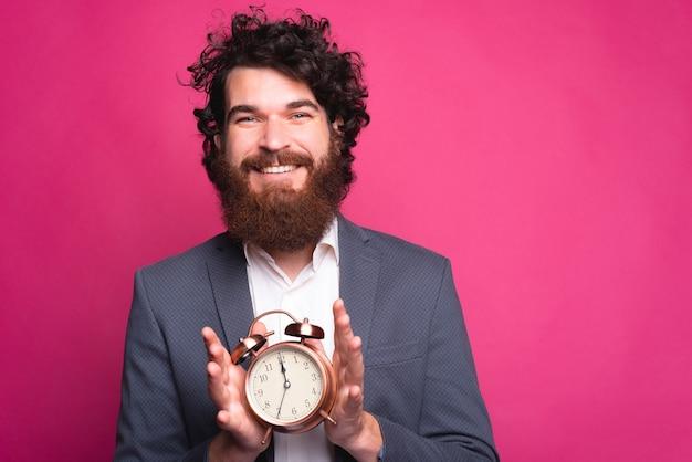Młody brodaty pozytywny mężczyzna trzyma okrągły zegar, uśmiechając się i patrząc w kamerę