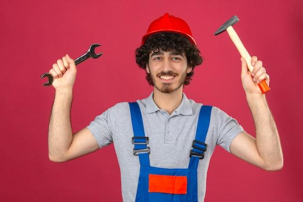 Młody brodaty przystojny budowniczy w mundurze konstrukcyjnym i kasku ochronnym, stojący z podniesionymi rękami, trzymając klucz i młotek, uśmiechając się wesoło nad izolowaną różową ścianą