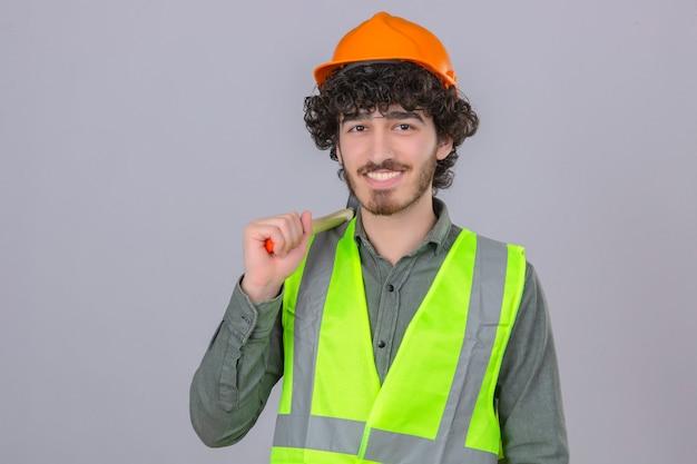 Młody, brodaty przystojny inżynier w hełmie ochronnym i kamizelce stojącej z młotkiem na ramieniu, uśmiechając się radośnie na odizolowanej białej ścianie