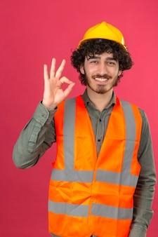Młody brodaty przystojny inżynier w hełmie ochronnym i kamizelce uśmiechnięty robi ok znak stojąc na odizolowanej różowej ścianie