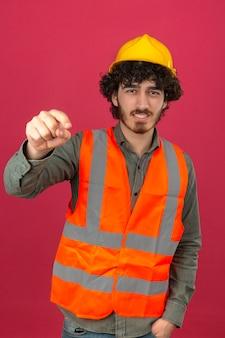 Młody brodaty przystojny inżynier w hełmie ochronnym i kamizelce wskazuje niezadowolony i sfrustrowany na kamerę zły i wściekły na ciebie na odizolowaną różową ścianę
