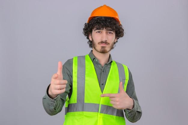 Młody brodaty przystojny inżynier w hełmie ochronnym i kamizelce wygląda pewnie, wskazując palcem wskazującym na aparat, uśmiechając się nad odizolowaną białą ścianą