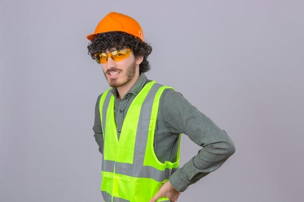 Młody, brodaty przystojny inżynier w okularach ochronnych hełmu i kamizelce uśmiechnięty przyjazny na pojedyncze białe ściany