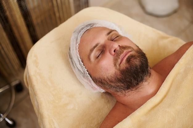 Młody brodaty przystojny mężczyzna leżący na stole do masażu w salonie kosmetycznym gotowy do leczenia uzdrowiskowego i kosmetycznego